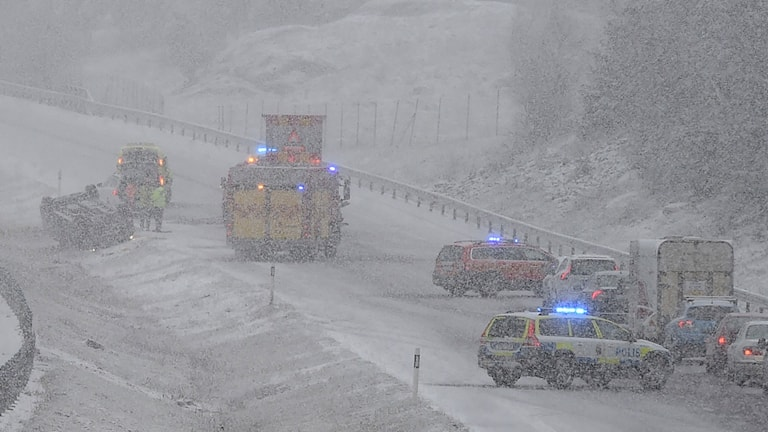 Bil voltat, snöig väg.