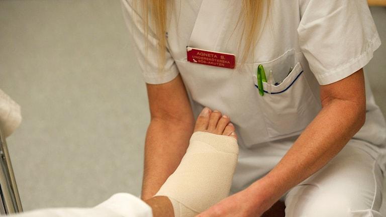 En undersköterska på akuten på Södersjukhuset lindar foten på en patient Foto: Leif R Jansson/TT.