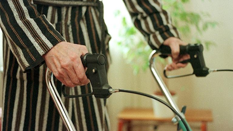 Äldre person med randig morgonrock greppar en rollator. Foto: Bertil Persson/TT.
