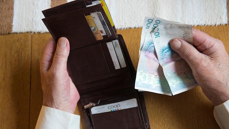 En person tar ut tre hundrakronorssedlar ur en plånbok. Foto: Fredrik Sandberg/TT.