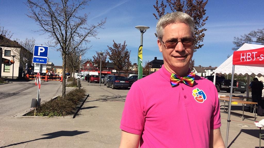 Robert Skoglund i rosa piké och regnbågsfärgad fluga