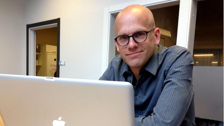 Andreas Ekström, kulturjournalist, föreläsare och författare, sitter vid sin laptop.