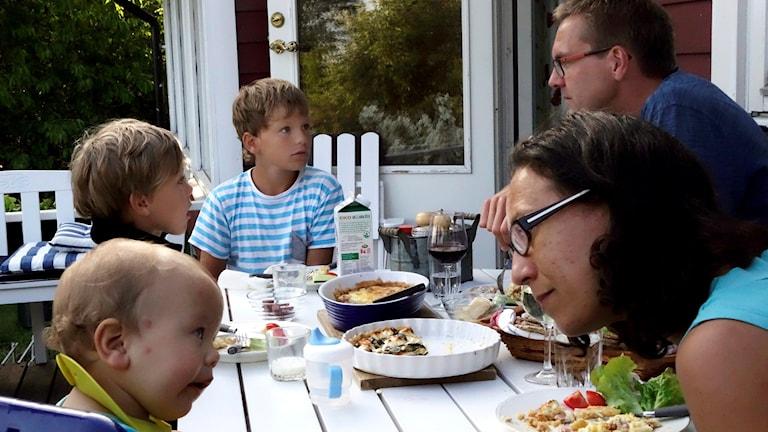 En familj äter ute på verandan en sommar.
