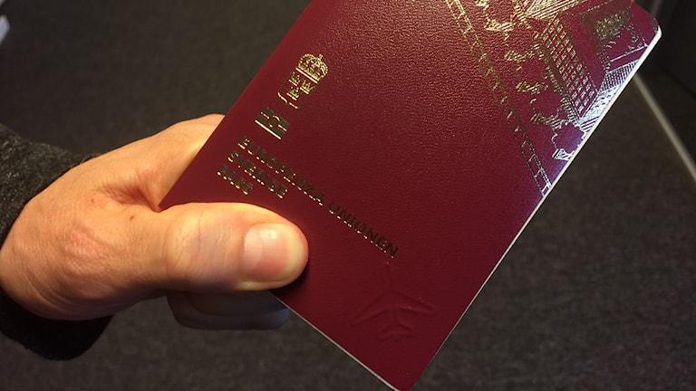 Ett pass som en man håller med vänster hand. Foto: Fredrik Blomberg/Sveriges Radio.