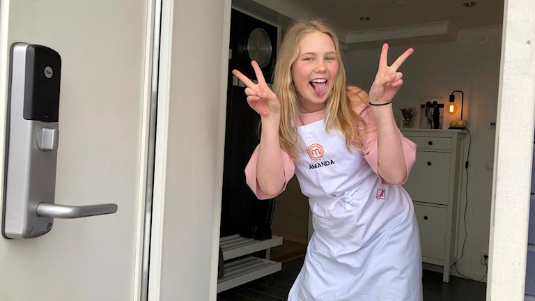 Amanda Stensson gör V-tecken i en dörröppning.