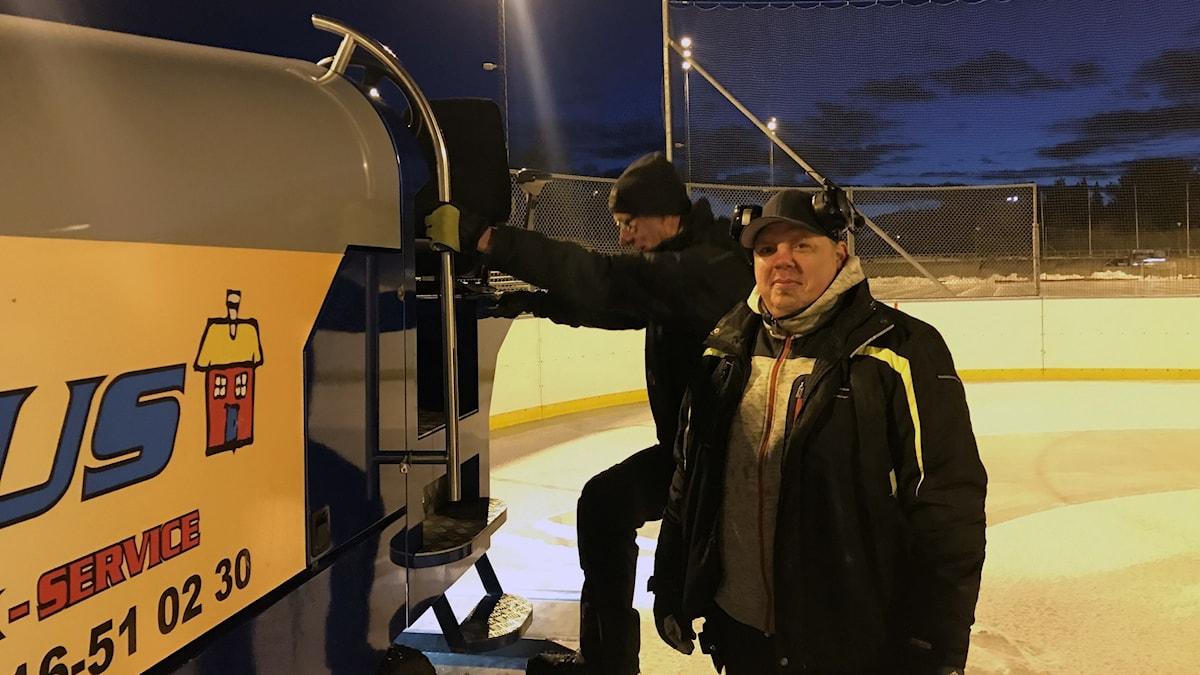 Två arbetsklädda män med mössa, den ena står på översta trappsteget till sätet på en ismaskin och den andra står nedanför på isen och tittar upp mot kollegan.