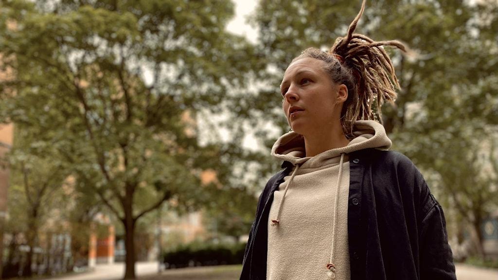 Musikern Kira Fors står utomhus med träd i bakgrunden.