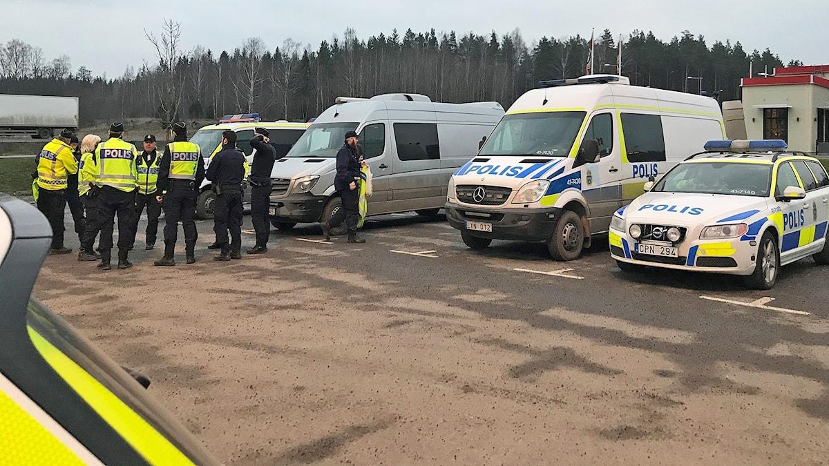 Trafikpoliser och flera polisbilar uppställda på parkering.