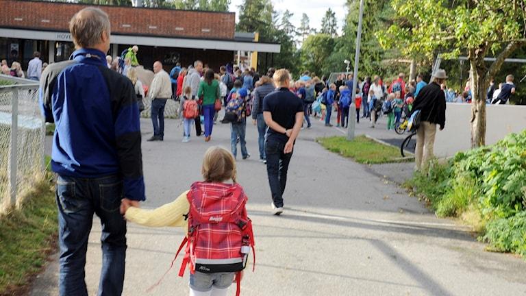 Förälder och barn utanför skola.