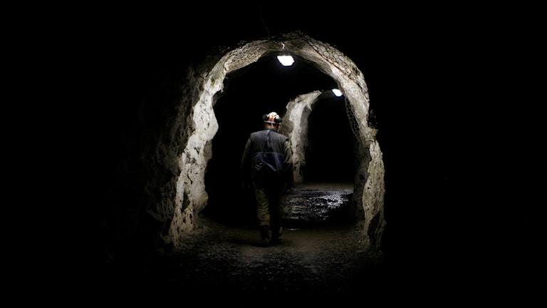 En gruvarbetare  går i en tunnel.
