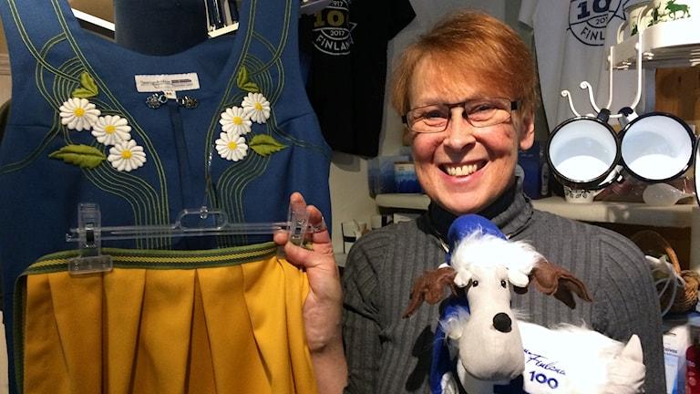 Kvinna står bredvid en Sverigedräkt och håller i ett gossedjur.
