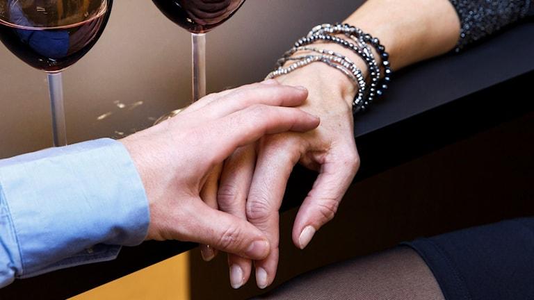 Manshand som ligger på kvinnohand.