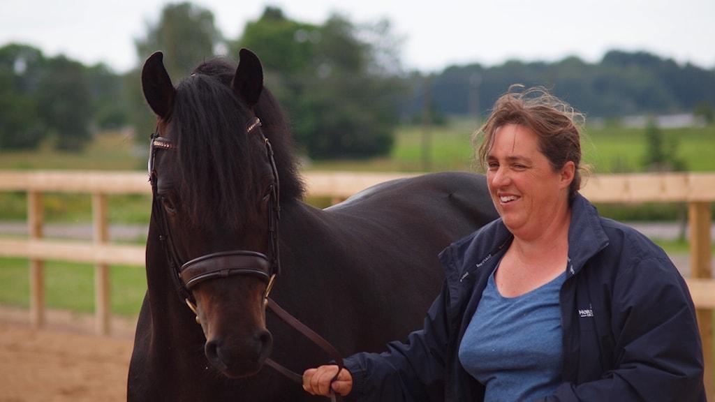 en kvinna med en häst.