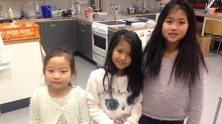 Tre flickor med mörkt hår i ett kök.
