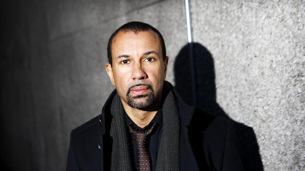 En man med mörkt hår och lite skägg framför en vägg, en svart skugga av honom till höger.