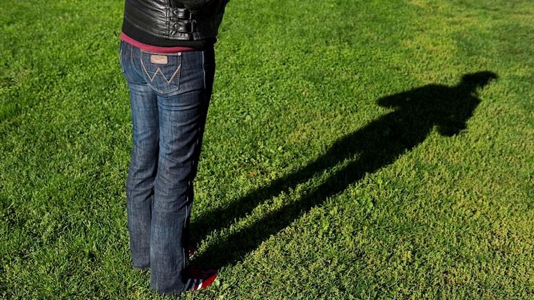 Kvinnoskugga över gräsmatta