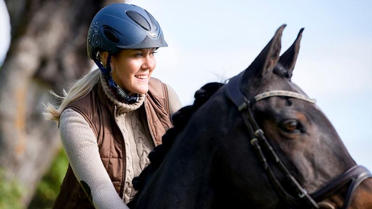 Karin Bjärle har på sig en blå hjälm och rider på en häst.