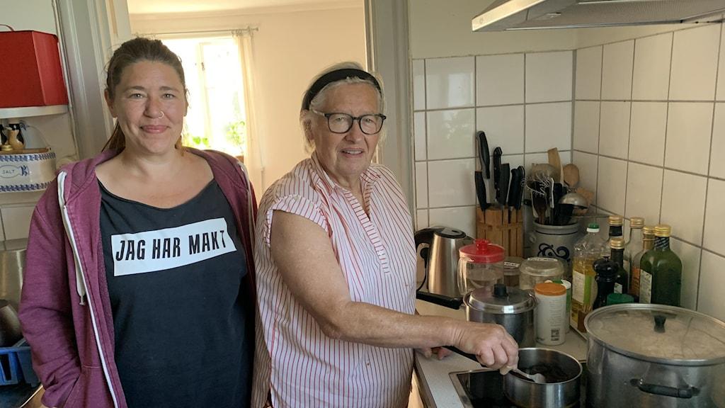 Två kvinnor står vid en spis, den äldre med grått hår i pannband och med glasögon rör i en kastrull.Den yngre kvinnan har en svart tröja på sig med texten Jag har makt.