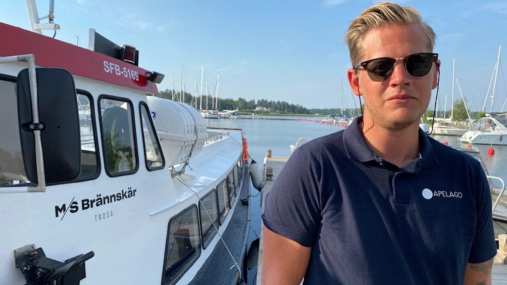 en man med solglasögon står framför en båt i en hamn.