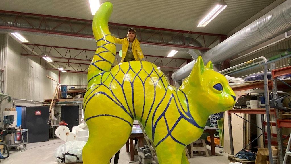 Tjåsa Gusfors, konstnär från Ålberga, syns ovanpå den gulgröna jättekatt som hon jobbar med i en verkstad i Nyköping.
