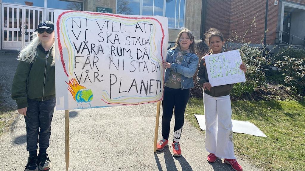 Tre skolelever som skolstrejkar för klimatet framför kommunhuset i Gnesta.