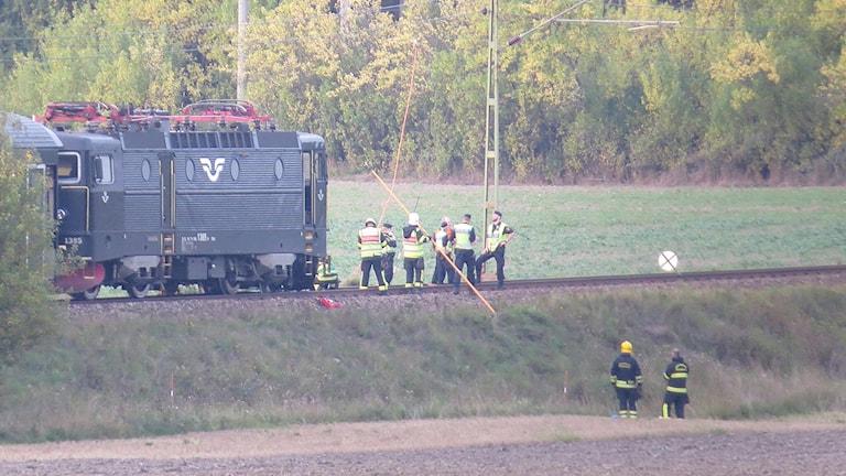 Ett tåg står på ett spår efter en olycka. Räddningspersonal finns i närheten. Foto: Dan Thun/Dagsmedia.se
