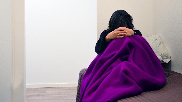 Kvinna under filt i säng. Ser ledsen ut