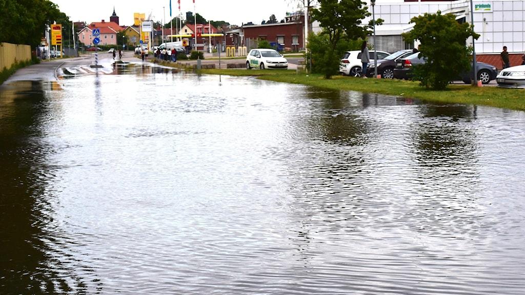En stor vattensamling, som en sjö över hela vägen och i bakgrunden bilar, en bensinstation, hus och en parkering.