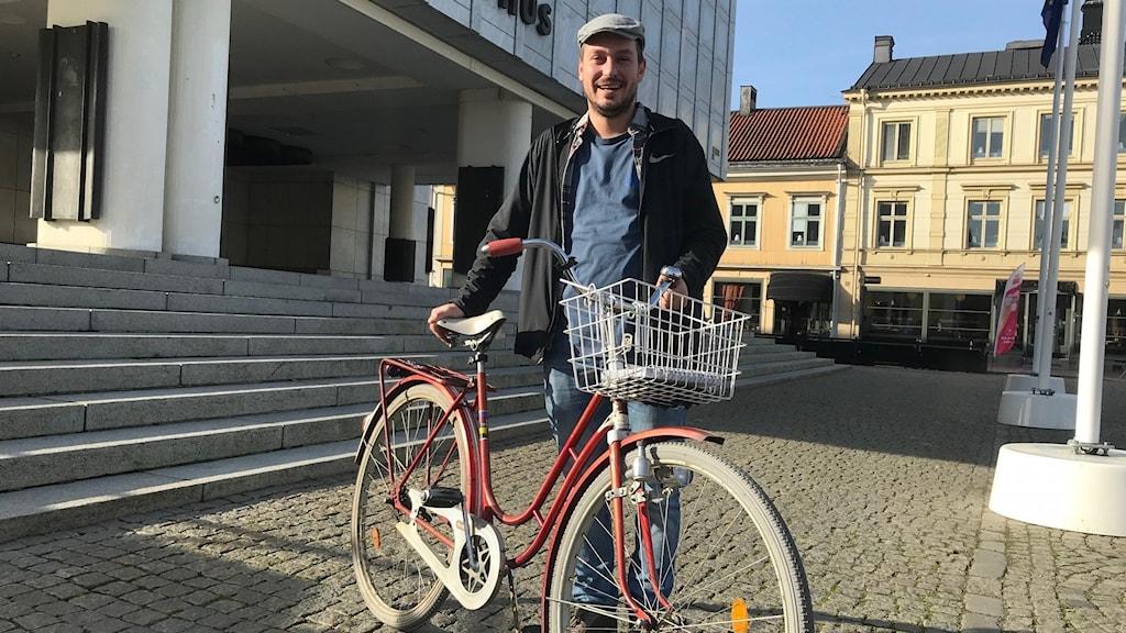 Labeat Bickay, strateg för hållbart resande på Nyköpings kommun. Står med sin röda gamla cykel framför Stadshustrappan i Nyköping.