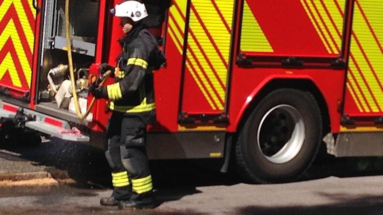 En brandman vid slangarna bak i brandbilen