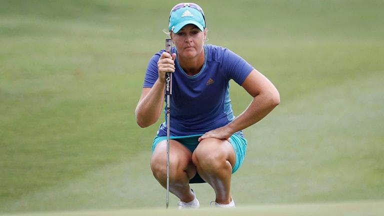 Anna Nordqvist på golfbanan, hukar och koncentrerar sig med klubban i hand. Foto:Joshua Paul/TT.