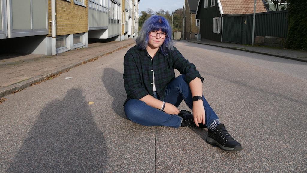 Micki från Katrineholm sitter på asfalten med husfasader som reser sig på båda sidor. Hon har blått hår och runda glasögon.
