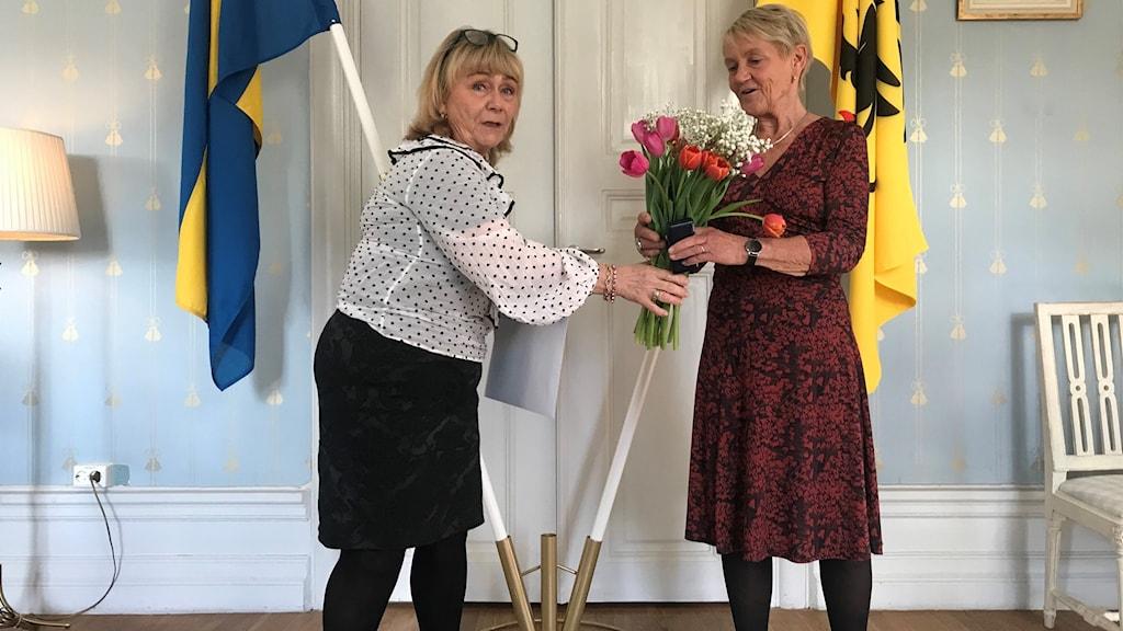 Cilla Krantz tar emot en bukett med röda tulpaner av Beatrice Ask.