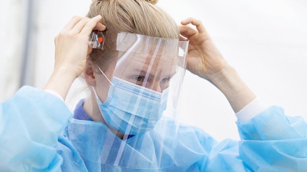 Vårdpersonal tar på sig ansiktsvisir och munskydd.