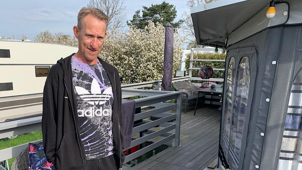 en man står på ett trädäck, uteplatsen till hans campingvagn. Bredvid honom sitter en schäfer.
