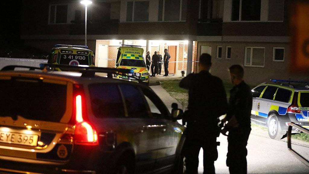 Polis och ambulans intill hus.