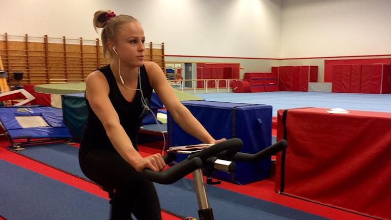Jonna Adlerteg på motionscykeln i Vilstahallen i Eskilstuna. Foto: Annizeth Åberg/Sveriges Radio.