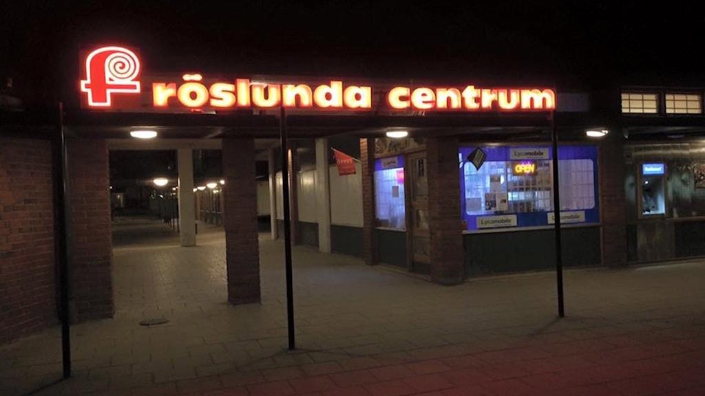 Fröslunda centrum med namnet på en neonskylt i mörker. Foto: Fredrik Blomberg/Sveriges Radio.