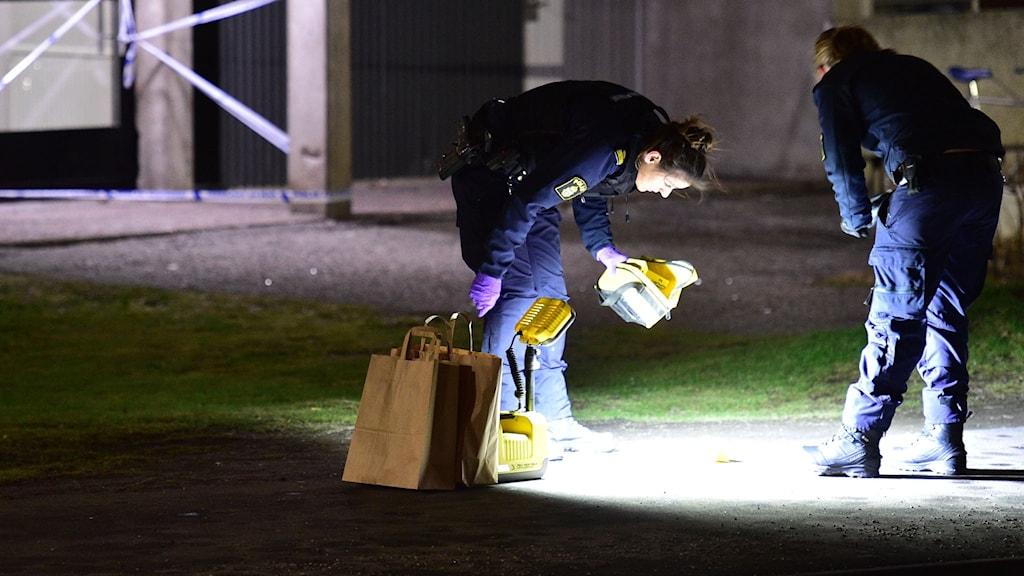 Två poliser genomför en teknisk utredning i Brandkärr i Nyköping. Den ena lyser med en lampa på marken. Foto: Pontus Stenberg.
