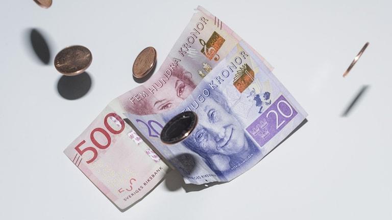Sedlar och mynt faller mot vit bakgrund.