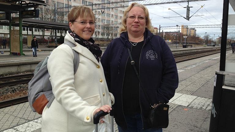 Två kvinnor står vid tågrälsen