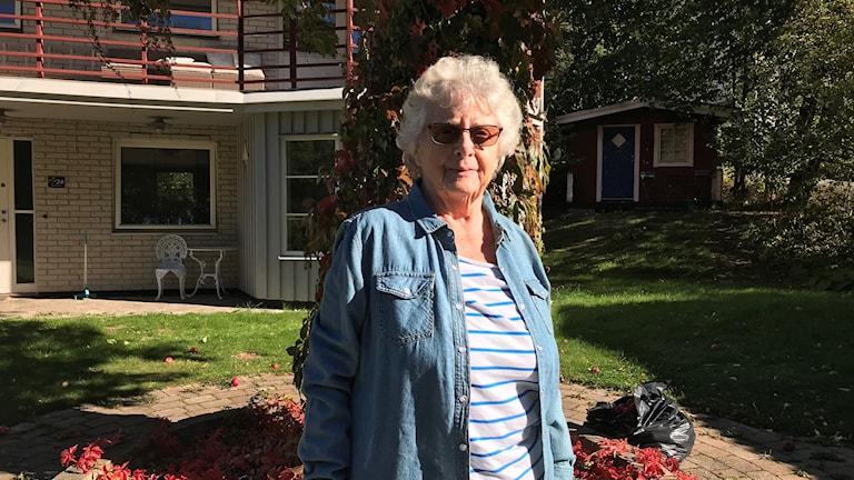 Kate Wohlstedt står framför ett träd i solsken.