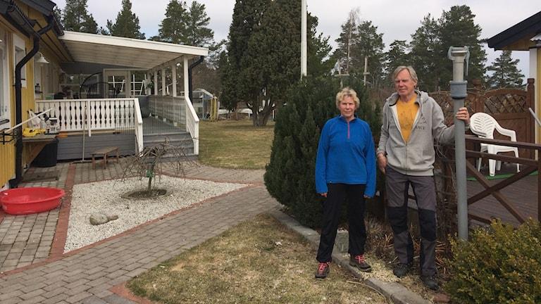Kvinna och man står utanför ett hus.