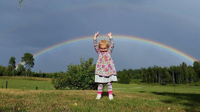 Flicka vid regnbåge.