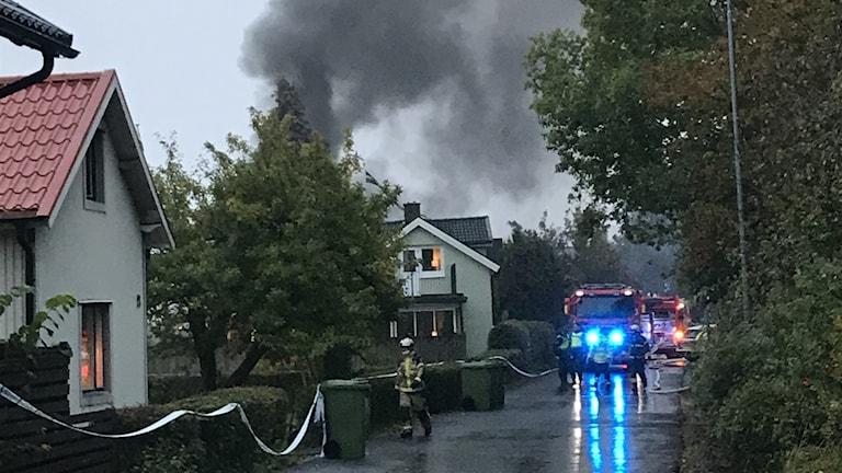 Bild på blåljusbil i villaområde. Rök stiger över husen.