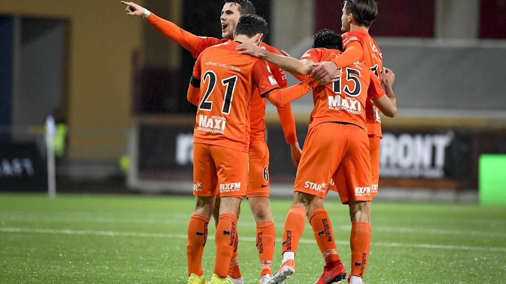 Orangeklädda fotbollsspelare jublar