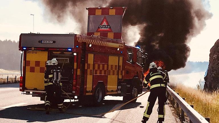 En brandbil och en brandman med en massa rök i bakgrunden