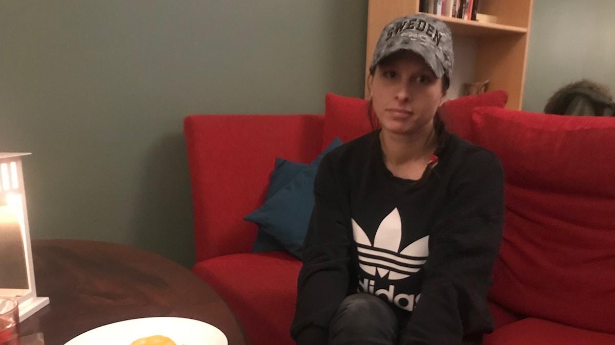 Kvinna i keps sitter i röd soffa med en tallrik mat framför sig på soffbordet.