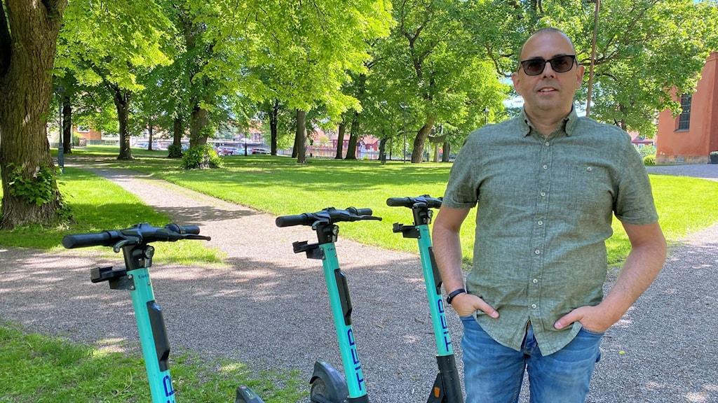 Man i mörka glasögon står framför tre elsparkcyklar som är parkerade på rad