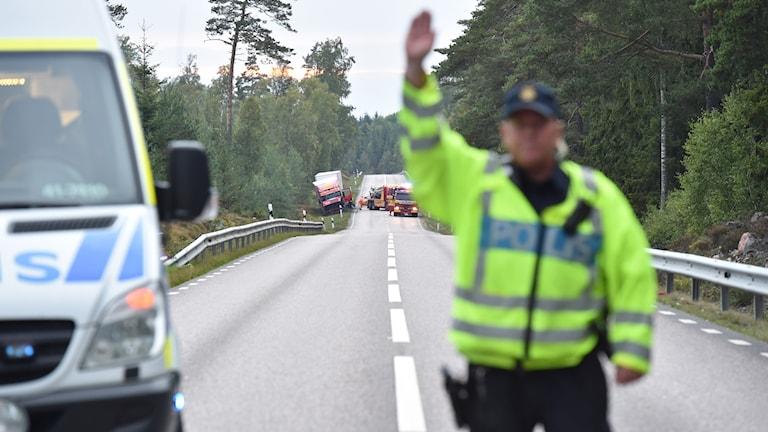 Polisman höger höger arm och stoppar trafik efter en dödsolycka på en riksväg. Foto: Pontus Stenberg.